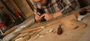 A man using a rotary tool and chisels to engrave wood.