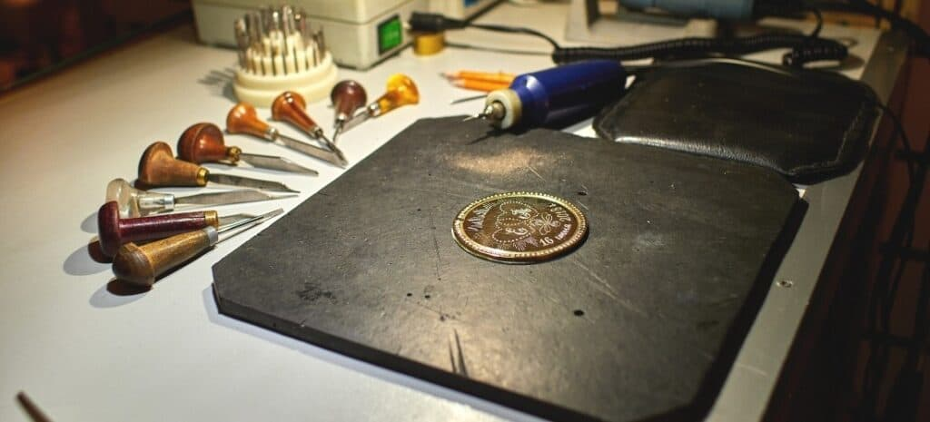 A recently engraved metal medallion surrounded by chisels, gouges, and a rotary tool.