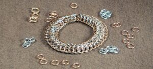 A silver and gold chain mail bracelet surrounded by scattered jump rings.