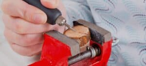 Woman using a rotary engraver on a round piece of wood held in a red vise.