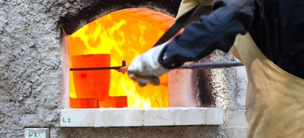 A crucible of molten glass being removed from a fiery furnace.