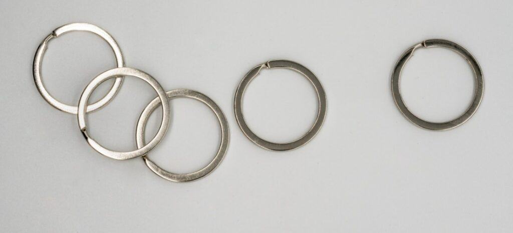 Five silver split rings against a white background.