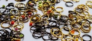 Colored jump rings and beads scattered across a table.