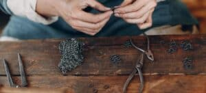 A woman linking jump rings together over a wooden table with rings and pliers scattered about.