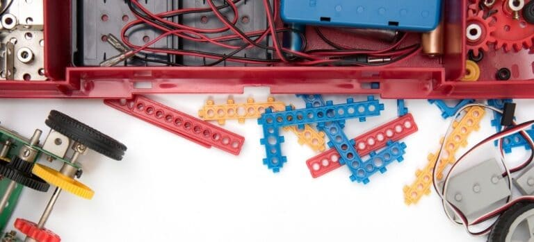 A yet unassembled STEM kit with various shaped parts, wheels, and wires.