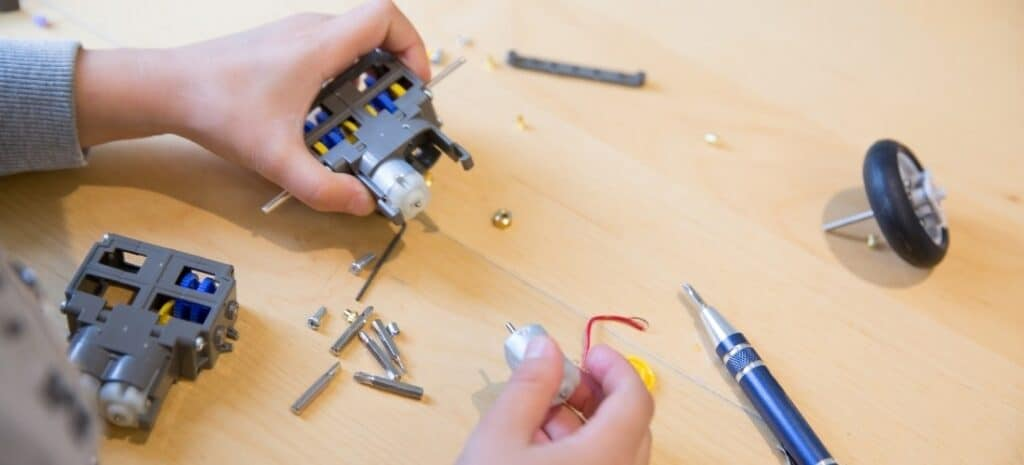 A young boy piecing together components and wires of a STEM model project.