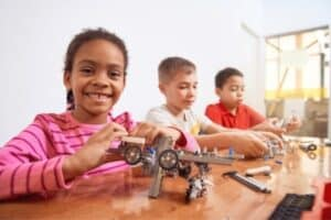 Three young students playing with STEM robotic toys.