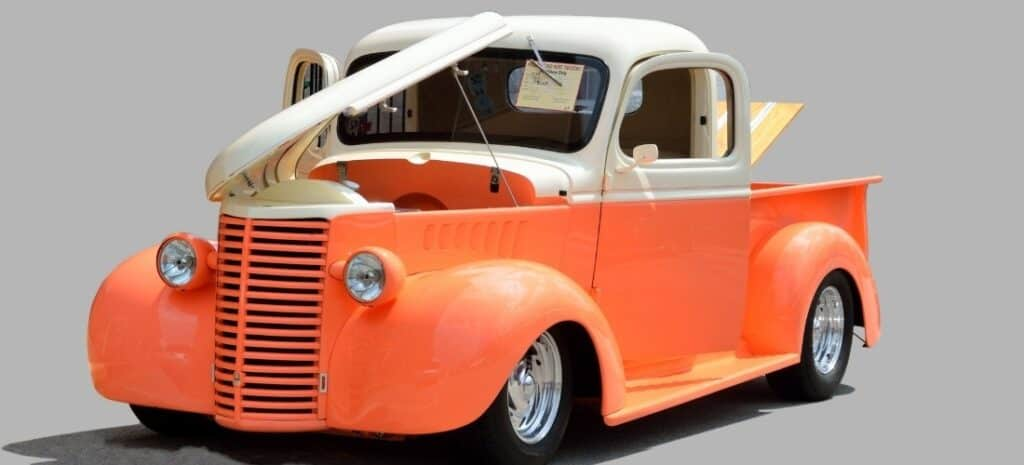 A model of a classic truck in orange and white.
