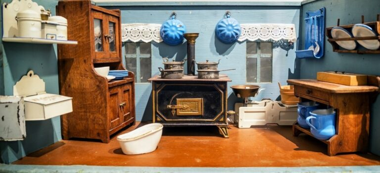 The kitchen of a dollhouse with wood cookstove and light blue accents
