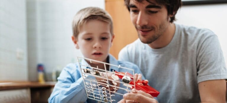 A father and son examining the pieces in a model car kit.