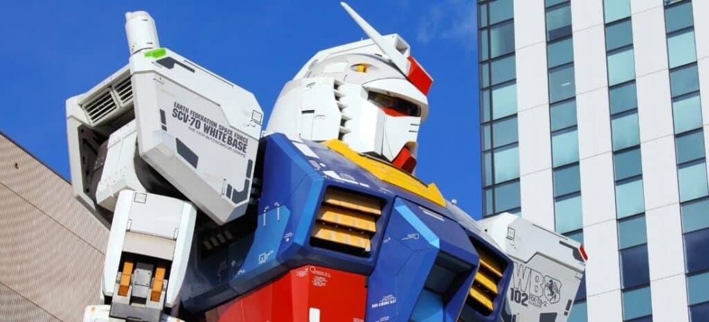 A Gundam action figure with a city building in the background.