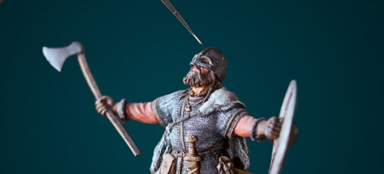 A paintbrush above a miniature Viking with a shield and an ax.