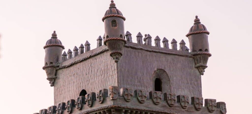 The top of a miniature castle tower showing the intricate construction details.