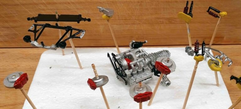 Small components of a model car kit mounted midair for painting.