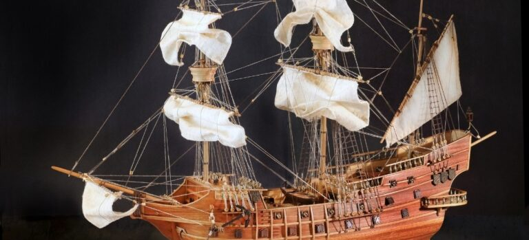 A wooden model ship with masts, sails, and rigging on a black background.