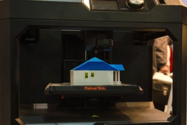 A MakerBot Replicator+ 3D printer finishing printing a model house with a blue roof.