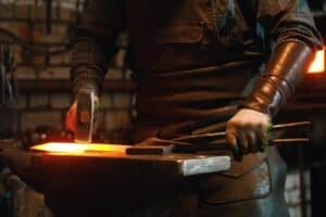 A blacksmith working with tongs and sledgehammer with a glowing forge in the background.