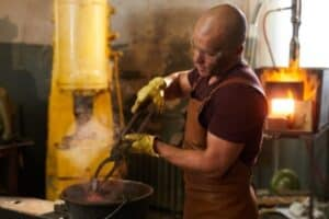 A blacksmith wearing apron using tongs to cool an item in water.