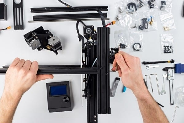 A man in the middle of assembling a 3D printer surrounded by various parts and tools.