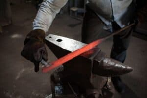 A blacksmith working on a red-hot rod balanced on an anvil.