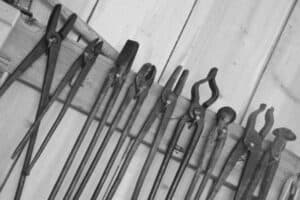 A black and white image of a collection of blacksmith tongs hanging on nails on a wall.
