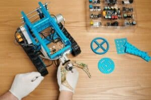 A man's gloved hands assembling a blue robotic vehicle kit.