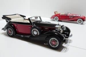 A black-and-red Mercedes roadster in 1/24 scale with another red Mercedes model in the background.
