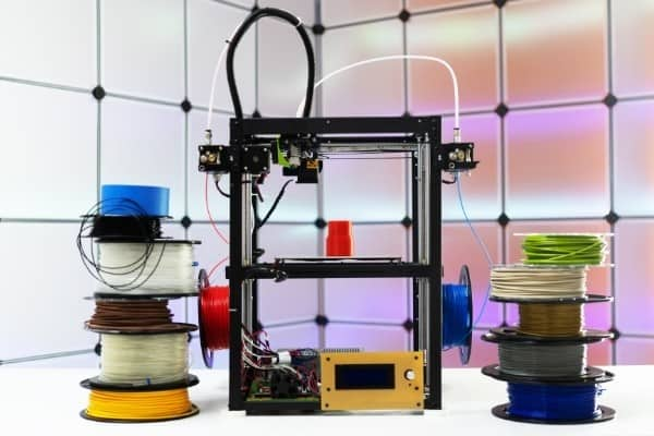 A 3D printer with various spools of filament on either side.