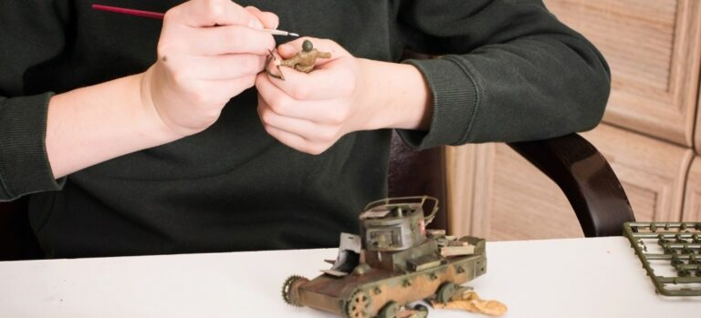 A young man painting a model soldier with a partially assembled tank on the table.