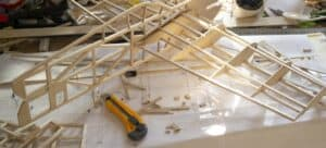 A nearly complete balsa wood model airplane and assorted parts and tools.
