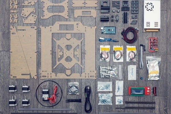 Various parts of a 3D printer kit laid out on gray wood table.