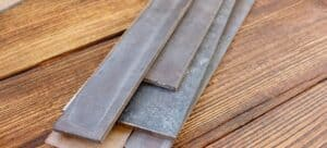 An assortment of steel blanks for knife making on a wood table.