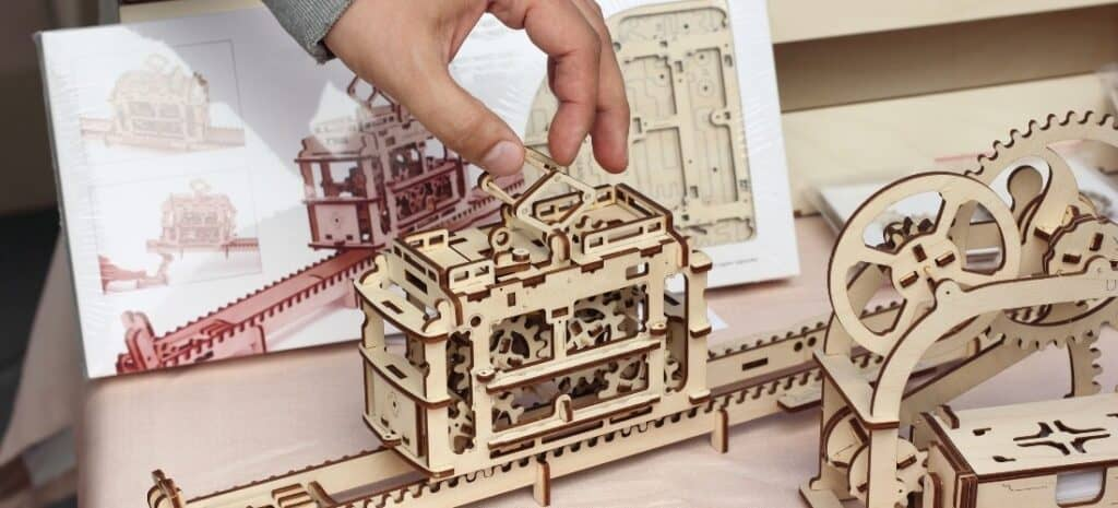 A man's hand applying a finishing touch to one of two wood 3D model puzzles.