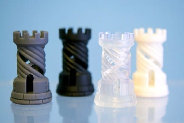 Gray, black, clear, and white 3D-printed resin chess pieces on a light blue background.