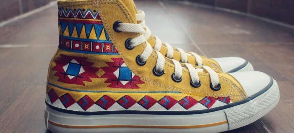 High-top canvas shoes painted with an Aztec-style theme.