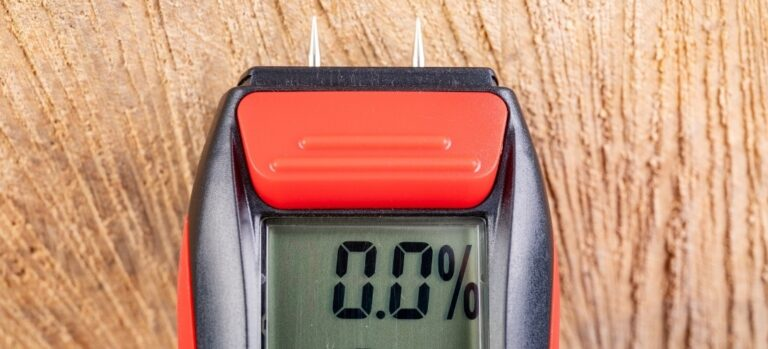 A black and orange pin-type moisture meter on a wood board.