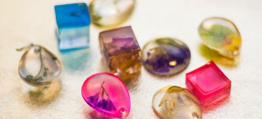 Resin pendants in different colors and shapes with embedded dried flowers.