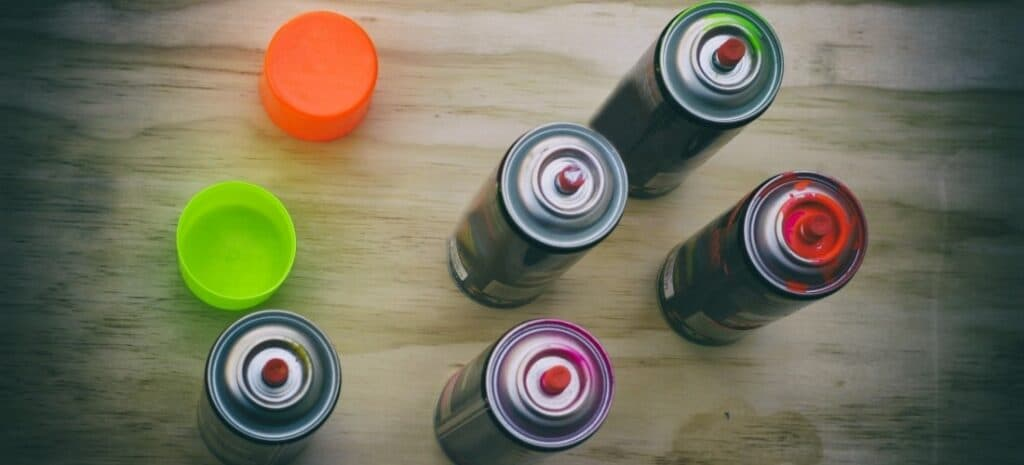 An overhead view of five cans of uncapped spray paint and two caps on a wood table.