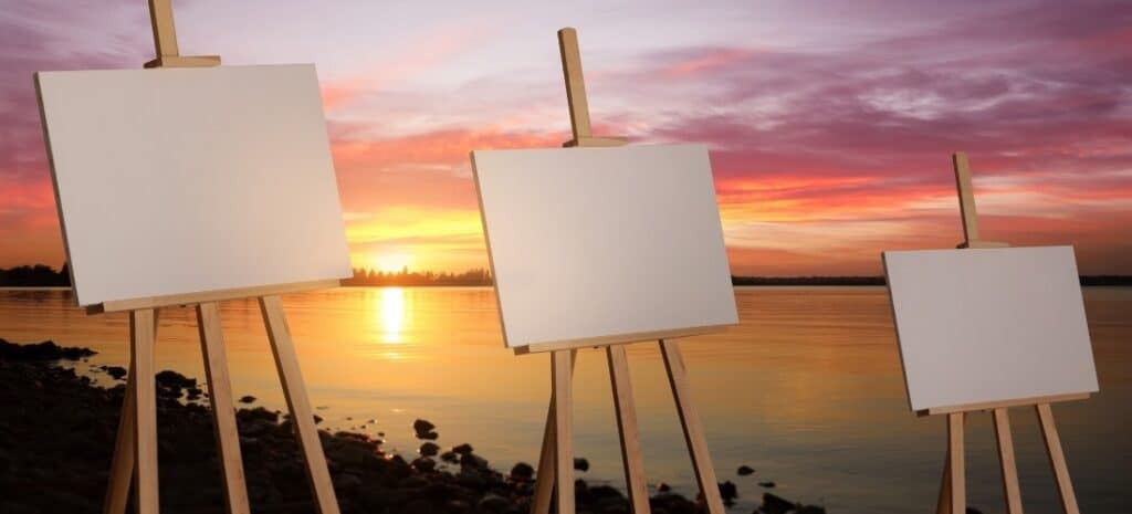 Three easels with blank canvases set on a riverbank with a lovely sunset in the background.