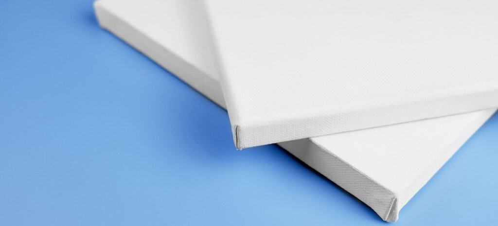 A light blue table with the corners of two white canvas boards resting on top.