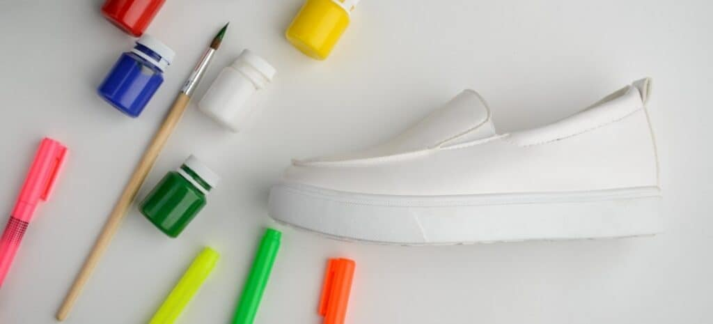 A white shoe with several bright jars of paint and fabric markers on a white background.