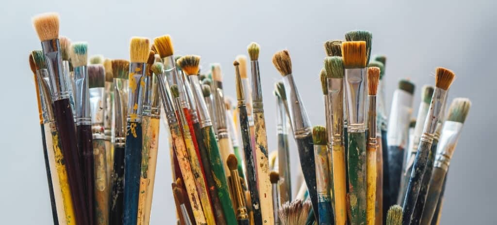 A large assortment of artist paint brushes in three cups.