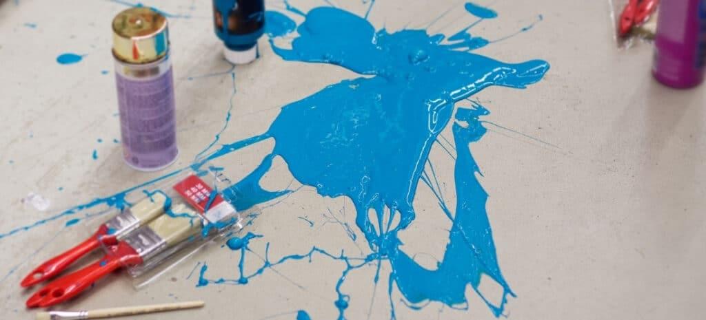 Blue paint spilled on a gray floor, splattering surrounding art supplies.