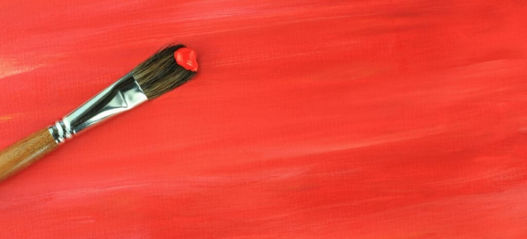 A paint brush with a dab of red paint resting on a paper that has just been painted red.