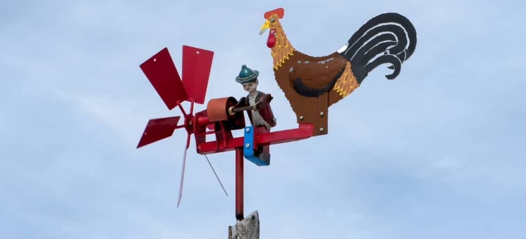 A custom-painted weathervane featuring a figure of a boy and a large rooster.