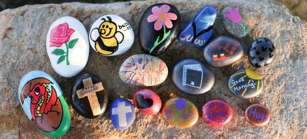 A variety of hand-painted garden rocks outside on a boulder.