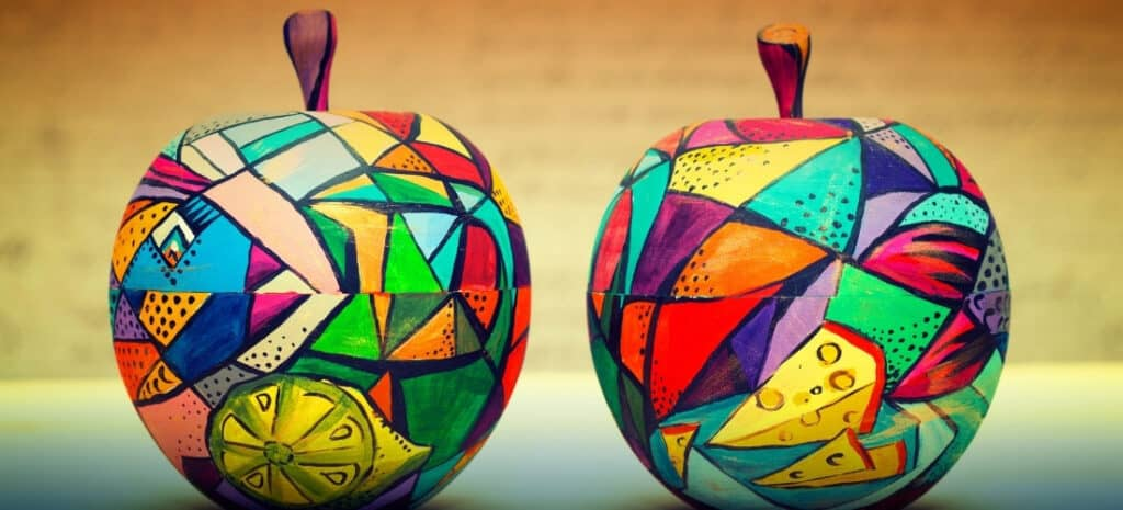 A pair of wooden apples that have been painted with various modern designs in an array of bright colors.