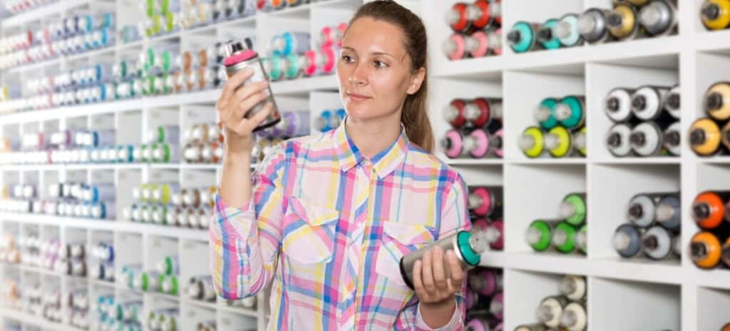 A woman examining two cans of spray paint while inside a store.